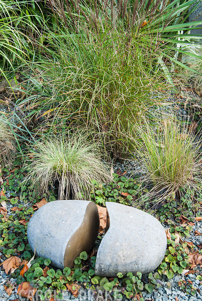 Stone sculpture with grasses on gravel surface. The Cors, Laugharne, Camarthenshire, Wales, UK