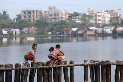 Children walk atop a fence at a lake locally referred to as Kalighatpur, near Science City in Kolkata, India. A shantytown li...