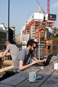 UK - London - A young man works at his laptop computer on the roof of the Boxpark - a so-called 'pop up mall' comprising of o...
