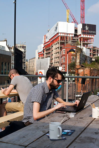UK - London - A young man works at his laptop computer on the roof of the Boxpark - a so-called 'pop up mall' comprising of old shipping containers