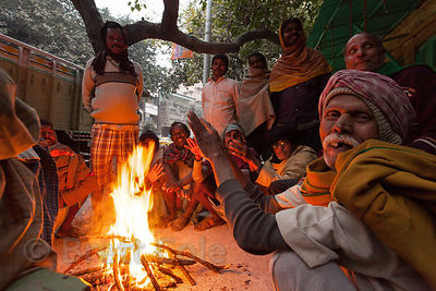 A group of men on a sidewalk gather around a fire for warmth, in the Sovabazar nieghborhood of Kolkata, India.