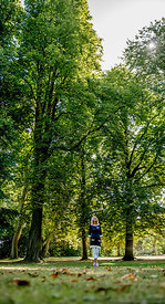 Nordic woman standing in front of tall trees