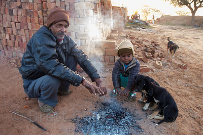 A man and boy sit with three street dog puppies next to a fire on a cold winter morning, Chachiyawas village, Rajasthan, India