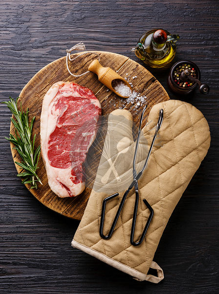 Raw fresh meat steak Striploin with salt and pepper and scissor tongs on cutting board on Black Burned wooden background