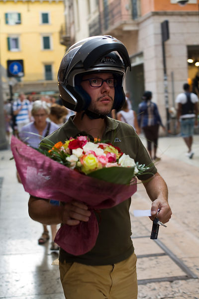 Italy - Verona - A man in a motorcycle helmet and keys about to deliver a bunch of flowers