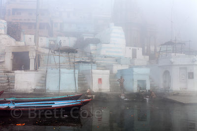 Boats on a foggy winter morning on the Ganges River, Varanasi, India.