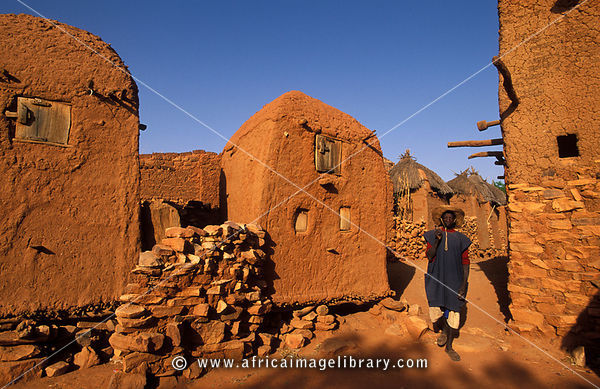 man returning from the fields , alley between granaries, Songo, Dogon Country, Mali