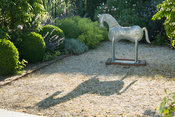 Galvanised metal horse stands on a gravel area beside pergola framed with box spheres and covered with roses and clematis, al...