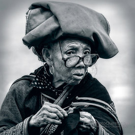 Older Red Zao Woman Sewing, Wearing Glasses