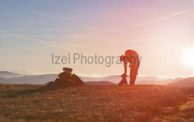 A hiker and their dog on a summit at sunrise on a winters morning in the Derwent Fells, English Lake Distrct, UK.