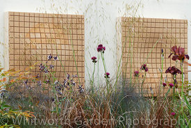 Cork wall sculpture artwork seen through planting including: Stipa gigantea, Cirsium rivulare, Carex, Aquilegea 'William Guin...