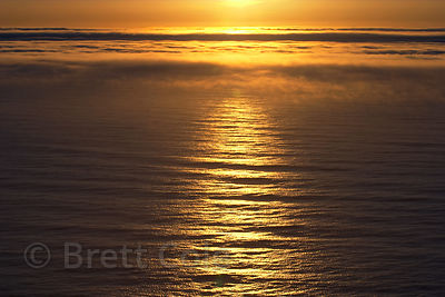The Pacific Ocean burns orange at sunset along the Oregon Coast.