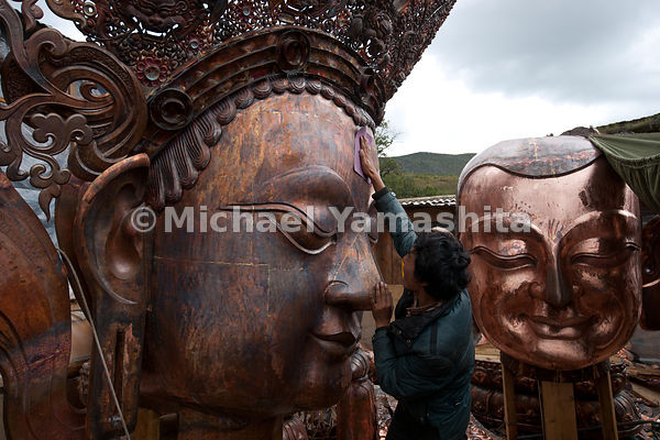 A craftsman polishes the nose of a gigantic copper Buddha at a monastery workshop in Shangri-La.