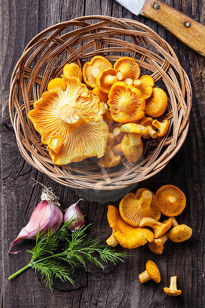 Raw chanterelles in basket on wooden texture