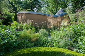 View towards Pond Garden surrounded by cob wall, topped with tiles and thatch, across box hedging, past Stipa gigantea, fenne...
