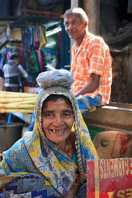 An elderly woman jokes around by putting a ball of clay on her head, in the Shyambazar area of Kolkata, India.