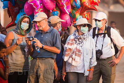 Foreign tourists cover their faces due to the air pollution from dust and smoke at the Pushkar Camel Fair, Pushkar, Rajasthan...