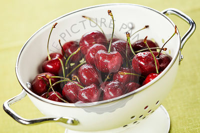 Wet ripe cherries in white colander