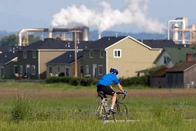 Cyclist passes housing subdivison and a sawmill in the West Eugene wetlands, Willamette Valley, Oregon