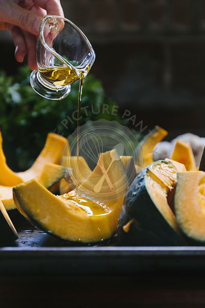 A woman is drizzling sliced kabocha squash with olive oil photographed from the front view.