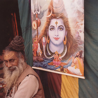 Pilgrims on their buA saddhu and a portrait of a god at the Kumbh Melas at the Kumbh Mela