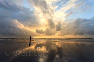 A boy walks on Juhu Beach in Mumbai, India at sunset, with clouds reflecting in the Arabian Sea.