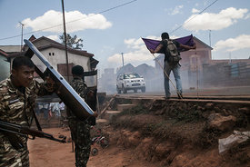 A man holds a banner as police officers clash with protestors during a demonstration in Soamahamanina (70 kilometer from Anta...