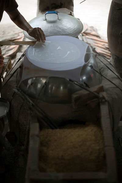 A woman makes fragile rice paper by hand