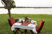 Dinner table on the bank of the Victoria Nile at Bakers Lodge, Murchison Falls National Park, Uganda