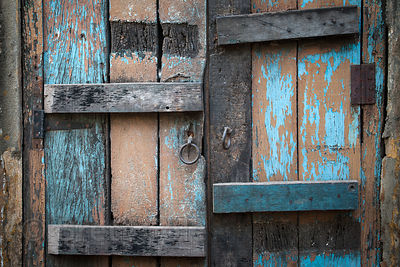 A weathered, blue-painted wooden door in Kolkata, India.