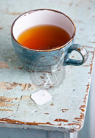 Cup of tea with teabag on blue textural background
