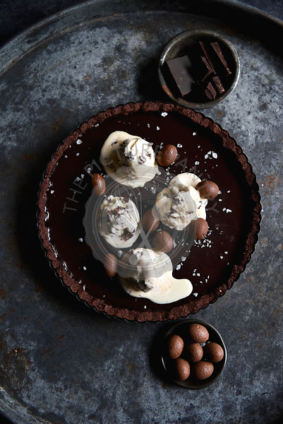 Chocolate tart with melting ice cream on a dark background