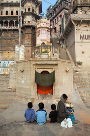 "Children watch a man ""wake-up"" an idol at a Hindu shrine in the morning, Varanasi, India. Idols throughout Varansai are put t..."