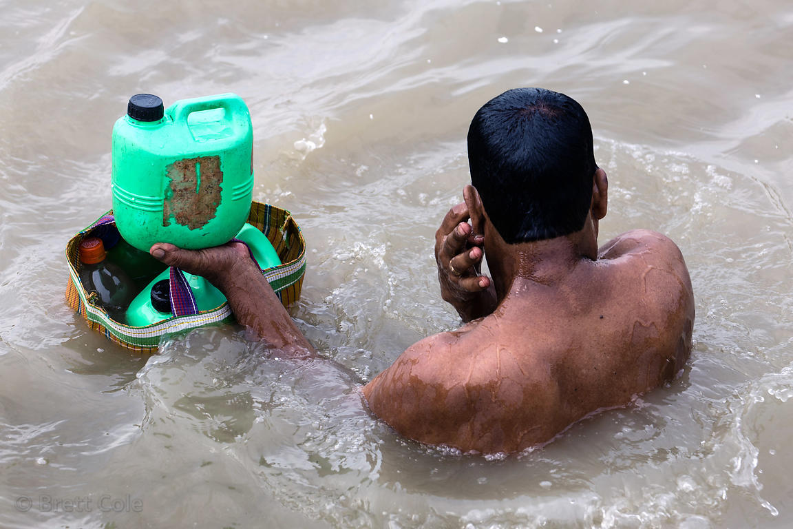 A man collects water from the Hooghly river, Babughat, Kolkata, India