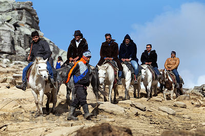 Indian tourists ride horses in rented fur coats at Snow Point on Rohtang Pass, Manali, India