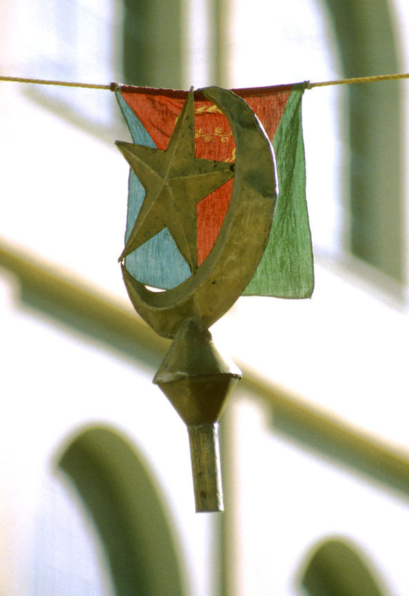 Photo: Sami Sallinen.February 1998..The Islamic symbols of the star and crescent grip the Eritrean flag after a flagpole is accidentally caught on decorations erected for Eid celebrations in the Eritrean capital Asmara. Preventing the rise of political Islam has been one of the main preoccupations of the Eritrean government since the country's formal independence in 1993. Eritrea's population is equally divided between Muslims and Christians.  The government formed by the Eritrean Peoples Liberation Front (EPLF - since renamed the Peoples Front for Democracy and Justice, PFDJ) has not allowed the formation of any opposition for fear of religious- or ethnic-based parties.