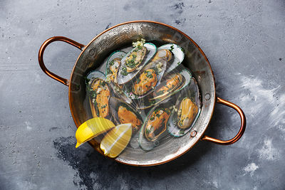 Shellfish Mussels Clams in copper cooking pan with parsley and lemon on concrete background