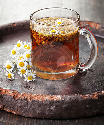 Chamomile tea with chamomile flowers on dark background
