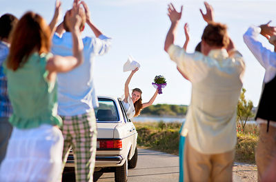 Bride waving to wedding party from car