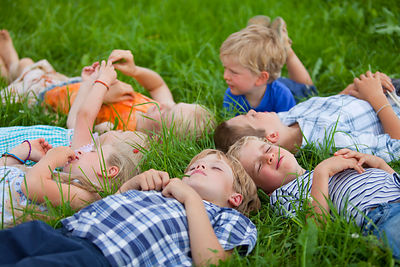 group of children lying in meadow, Memmingen, Bavaria, Germany
