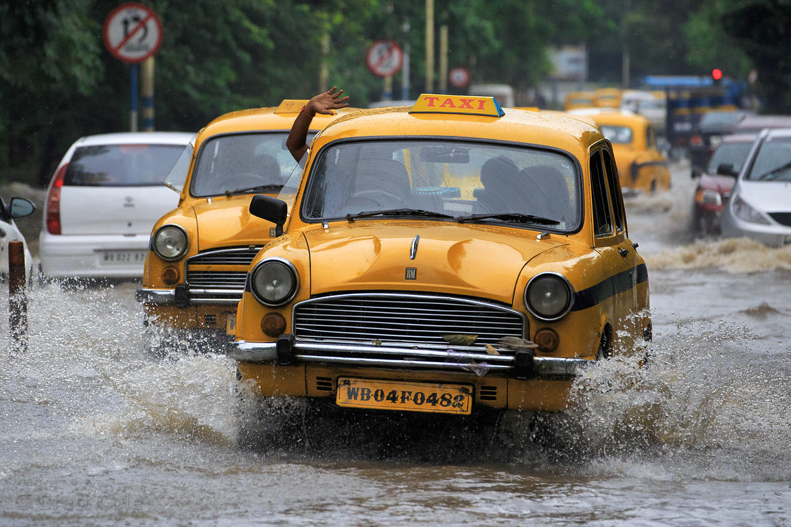 Taxis and other cars drive in flooded streets, Maidan, Kolkata, India. Taken during the heaviest rains in Kolkata in a decade.