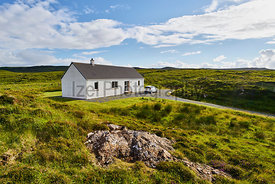 A remote white painted house near Dunvegan on the Isle of Skye, Scotland, UK.