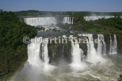 Iguassu (Iguazu) Falls from the Brazilian side, with tourists in boat getting soaked under waterfall