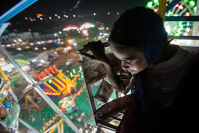 A girl rides a ferris wheel at night at the Pushkar Camel Mela, Pushkar, India.