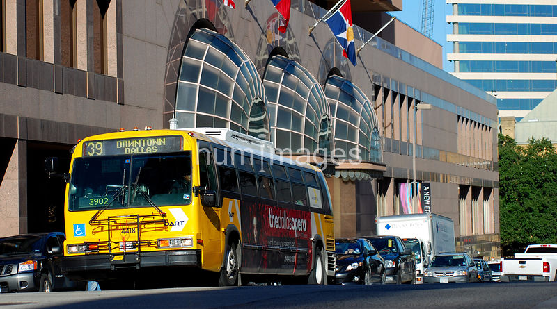 Yellow DART bus in downtown Dallas traffic
