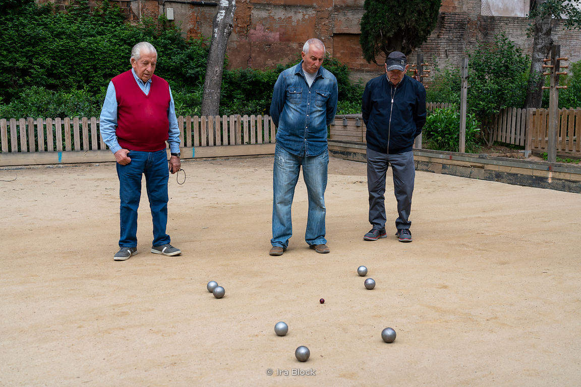 A group of men playing a game of bocce at a park in Barcelona, Spain