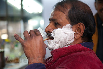 A man drinks chai tea as he gets a haircut, Jodhpur, Rajasthan, India