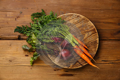 Fresh vegetables carrots and beets on round cutting board on wooden background