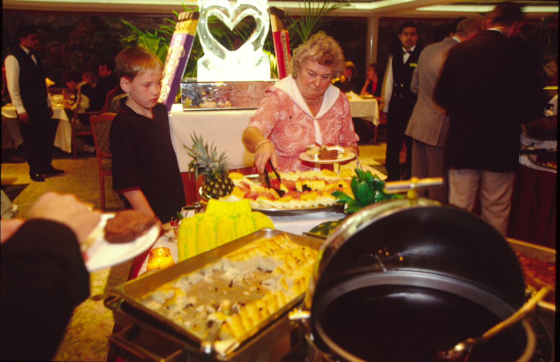 Passengers load their plates with food at a buffet on board the P&O Cruise Liner Oriana