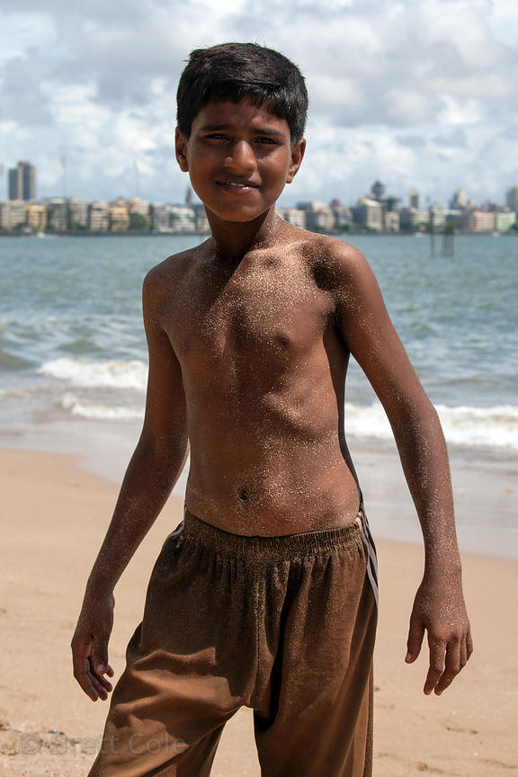 A fishing boy on Chowpatty Beach, Mumbai, India. They work on boats and also reel in nets by hand by walking out into the wat...
